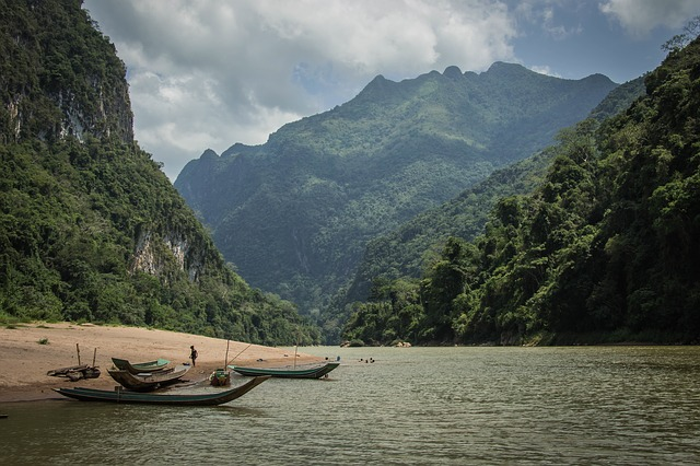 A small boat in a body of water with a mountain in the background